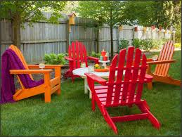 wood fencing for contemporary backyard decoration with green grass and white coffee table plus plastic adirondack