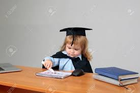 cute boy small child in black squared hat and academic gown sitting at wooden school desk