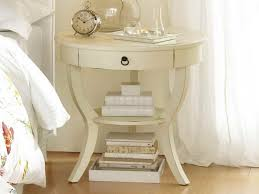small cream bedside tables with round bedside table and books also drawers