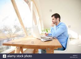 home office multitasking. Portrait Of Young Businessman With Hand On His Chin Sitting In Front Laptop And Doing Home Office Multitasking C