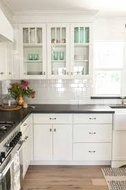 white shaker cabinetry with glass upper cabinets as featured on from kitchen backsplash ideas for white cabinets black countertops