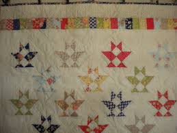 A Primer on Quilt Settings & White Quilt with Triangle Pattern and Colorful Border Adamdwight.com