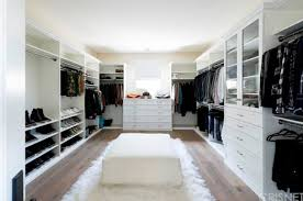 large modern closet featuring a hardwood flooring topped by a soft rug and a chair