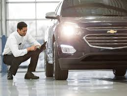 buick cadillac chevrolet service technician checking on tires of suv