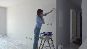 home office multitasking. brilliant office young woman talking on cellphone while painting wall at her new home  4k  stock video in home office multitasking