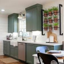 shiplap wall kitchen. country kitchen with indoor herb garden, sage green cabinets, and white shiplap walls wall s