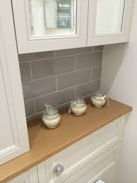 tiling kitchen wall white ceramic tile backsplash modern wooden island white polished wood countertop table modern