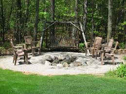 surrounding a stone fire pit with gravel is a great way to stay under budget while still being conscious of fire hazards the a frame swinging bench adds