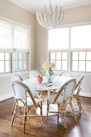 illuminated by a glossy white leaves chandelier an oval saarinen dining table is surrounded by serena lily riviera side chairs placed in front of windows