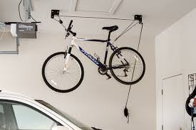 The Up and Away Deluxe Hoist System bike rack and bike mounted to a garage  ceiling