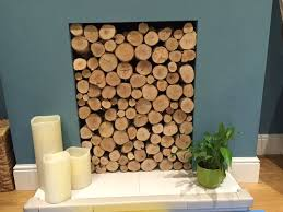silver birch round logs all hand finished at one end stacked beautifully in a unused fireplace