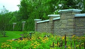 tranquil garden with black eyed susans flowers protected by a concrete wall that looks like stone