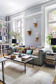 a cozy pastel living room with a light grey chesterfield sofa and lots of books