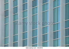 office glass windows. Exterior Windows Of A Modern Steel And Glass Commercial Office Building Reflecting Blue Sky - Stock