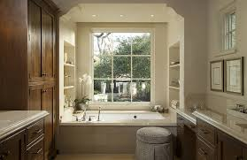 traditional bathroom features an alcove filled with a tiled tub accented with a deck mount tub filler situated under window flanked by built in shelves