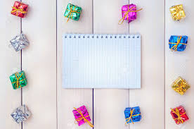 bo with gifts on a light wooden boards white notepad happy new year