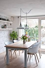 modern dining room decor featuring an exposed brick wall painted white open shelves white side chairs and two vine industrial pendant lights over the