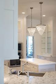 two pottery barn clarissa crystal drop small round chandeliers hang over a small kitchen island next to a microwave stacked atop a wall oven