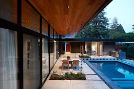 view in gallery sliding glass doors and glass walls connect the living area with the landscape and pool outside