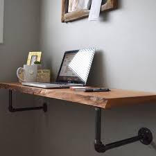 perfect for stylish space savers this minimalist wall mounted live edge desk is finished from rough sawn reclaimed hardwoods walnut cherry