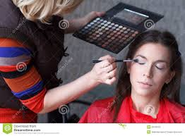 makeup artist preparing attractive brunette model eyeshadow before photo shoot