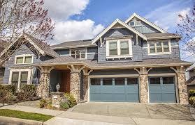 bright blue garage doors on darker blue house with white window trim