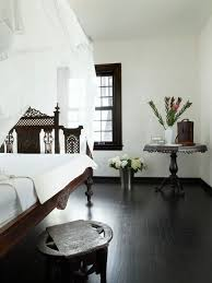 Example of a tuscan dark wood floor and black floor bedroom design in Miami  with white