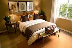 Again utilizing decorative pillows in place of a headboard, this brown and  orange bedroom makes