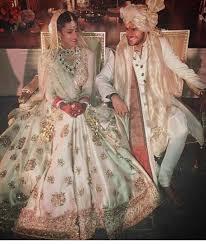 image via bride wearing a cream sabyasachi lehenga grooms adorns a raghavendra rat sherwani