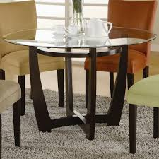 round glass dining table with dark brown wooden base on grey fur rug in inspiring round