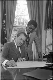 best richard pat nixon images american  president richard nixon signing a document at his desk in the oval office as sammy davis