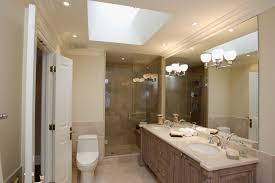 Mirror sconces, recessed lighting, and a skylight work together to  highlight this lovely bathroom