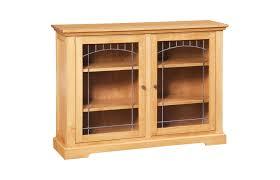 short light brown wooden bookshelf with double glass doors and rack inside