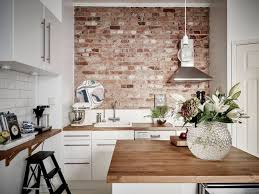 kitchen red unique brick wall black marble countertop brown wooden countertop laminated wooden floors brown marble