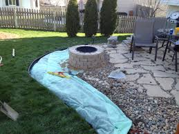 stone fire pit and flagstone pavers in backyard garden