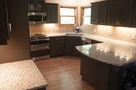 furniture black wooden kitchen cabinet and grey granite countertops connected by beige tile backsplash