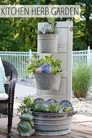 tiered kitchen herb garden made from an old door and galvanized buckets