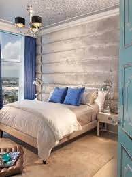 a light grey and silver bedroom infused with bold blue pillows and curtains of this
