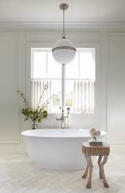 ralph lauren hendricks pendant over a white freestanding oval tub in a transitional bathroom boasting honed calcutta gold herringbone bath floor tiles