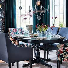 a black round dining table and chairs upholstered with a fl fabric