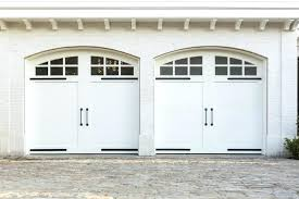 arched garage doors this bright white brick home features two car garage with white painted wood