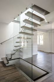 Side view of modern floating staircase with oak treads and glass railing  leading to second floor