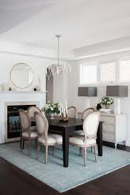 blue and brown dining room features a whitewashed french candle chandelier illuminating a dark brown dining table lined with french round back dining chairs