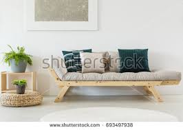 cupboard furniture design. trendy beige sofa with navy blue pillows and wooden frame cupboard plants in simple furniture design