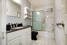 Bathroom With White Vanity With Black Counter Top And Black Toilet ...