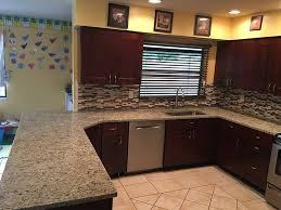 giallo ornamental granite countertops with backsplash tiles