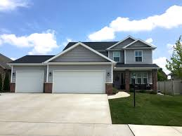 two story home with grey siding and grey shakes black roof eyebrows over garage