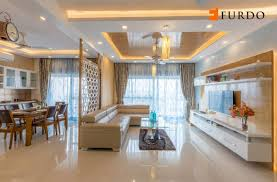 the living room with l shaped sofa and artistic false ceiling