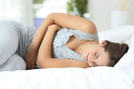dr paul mackoul md minimally invasive gyn surgeon girl suffering menstrual pains lying on the bed at home