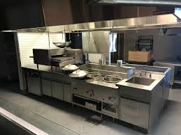 Hand sink, wok, chef table with used impringer, (not included) space for a  rolling warmer box (shown bottom left) and storage space.